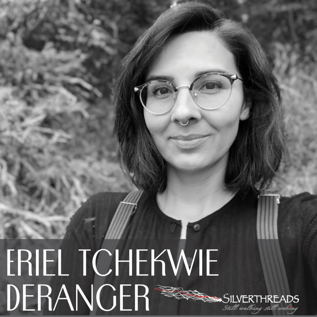 Black and white photo of Eriel Tchekwie Deranger with trees and bushes in the background. She has dark shoulder length hair, glasses and a septum ring. She is wearing a black ribbed t-shirt with buttons and suspenders over her shoulders. There is a Silver Threads logo in the lower right corner.