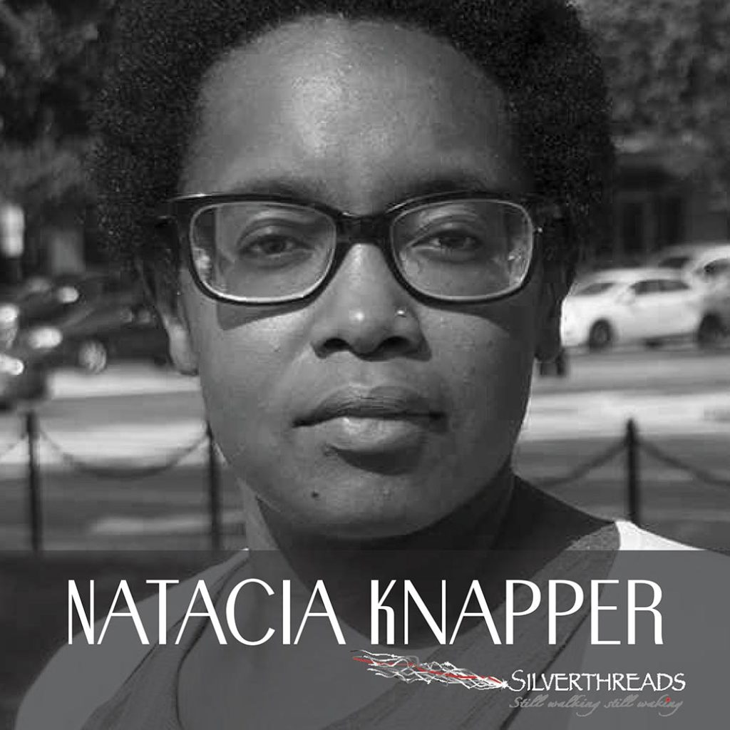 """Black and white photo of a person lookign directly into the camera. THey are wearing glasses and the photo is cut off at their shoulders. A transparent grey box at the bottom holds the text """"Natacia Knapper"""" and the Silver Threads Logo is in the bottom right corner."""
