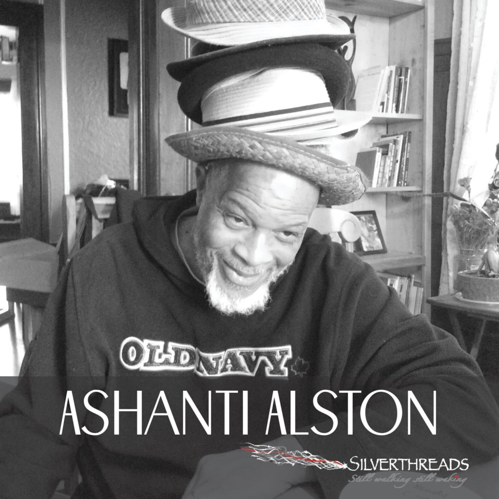 Black and whit photo of Ashanti, wearing a dark hoodie and which several different types of hats piled on top of his head.