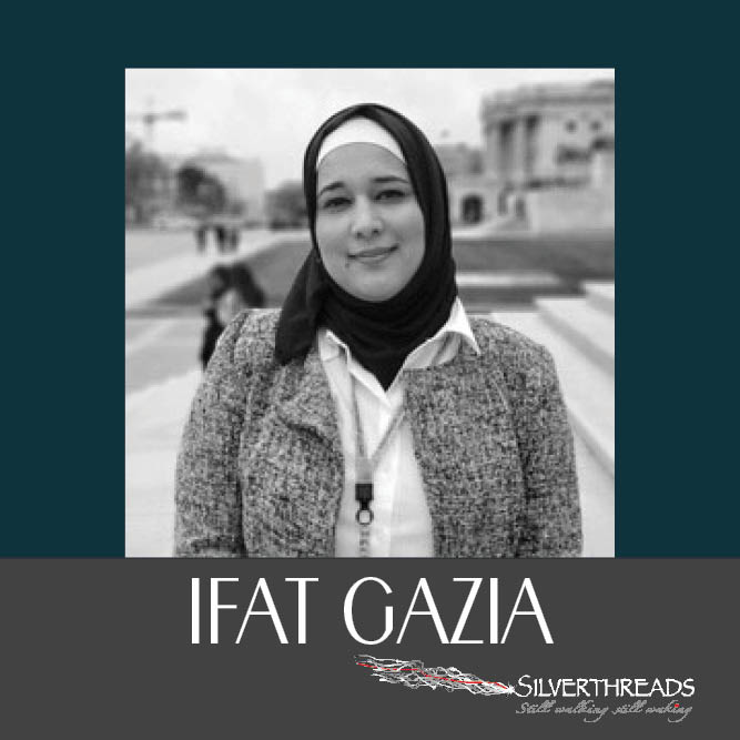 "A black and white photo is centred on a dark green background. In the photo, a person is looking directly at the camera. THey are wearing a grey wool jacket and a white button shirt underneath. They are wearing a dark hijab and the image is cut off at their bust. A dark gray stripe at the bottom holds text that reads ""Ifat Gazia"" the silver threads logo is in the bottom right corner."