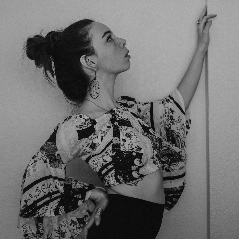 A black and white photo of a person facing to the right of the image. Their left arm is lifted, the hand resting on a wall in front of them. They are wearing a patterned shirt with flowing sleeves. The image is cut off at the hips.