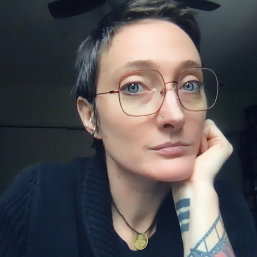 A person is looking directly at the camera. They rest their chin on their left hand, which has some visible tatoos. They are wearing glasses and a dark top. The image is cut off at the shoulders.
