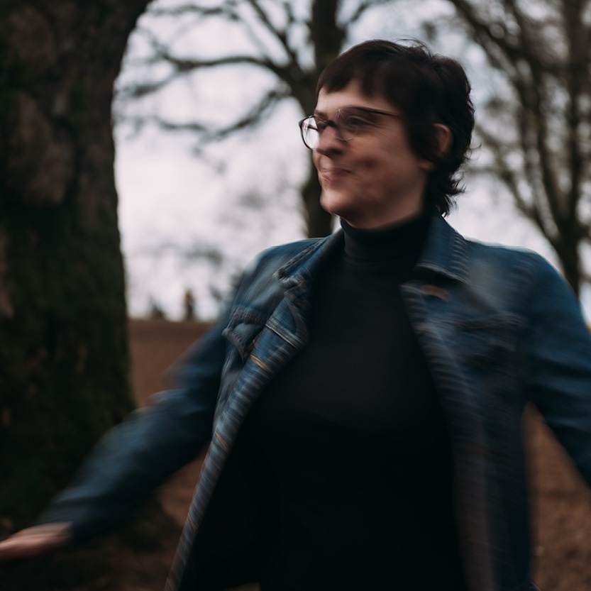 In motion graphic of person near a tree. They are wearing a jean jacket and glasses. The image is cut off at their waist and their arms are out to the side. They are spinning, captured in a still photo.