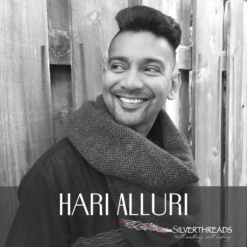 "Black and white photo of Hari. He looks to the left of the image and is smiling. He is leaning against a wooden fence and is wearing a big scarf. A transparent dark grey box at the bottom holds text that reads ""Hari Alluri"" and has the silverthreads logo in the bottom right corner."