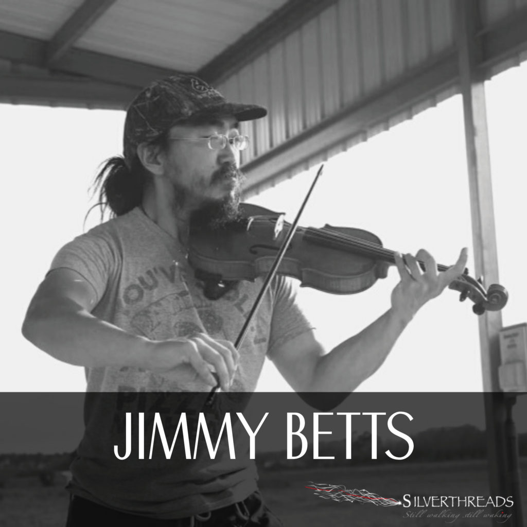 "A black and white photo of Jimmy playing the violin. They are wearing glasses, a ball-cap and t-shirt, with their hair back in a loose bun. They're outside in a covered space, with the wide open sky, field and trees behind them. The text below reads ""Jimmy Betts"" and there is a Silver Threads logo in the bottom right corner."