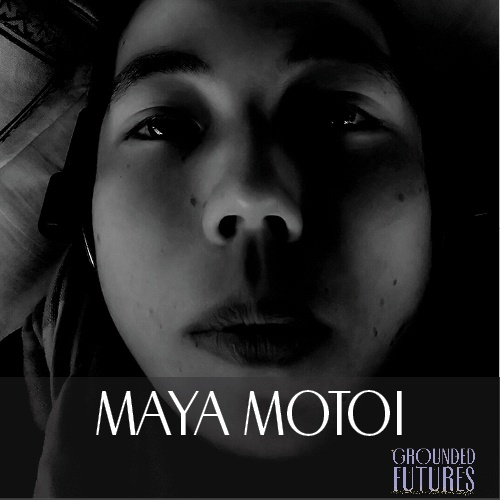 Black and white photo of Maya, close up of their face, with heavy shadows.