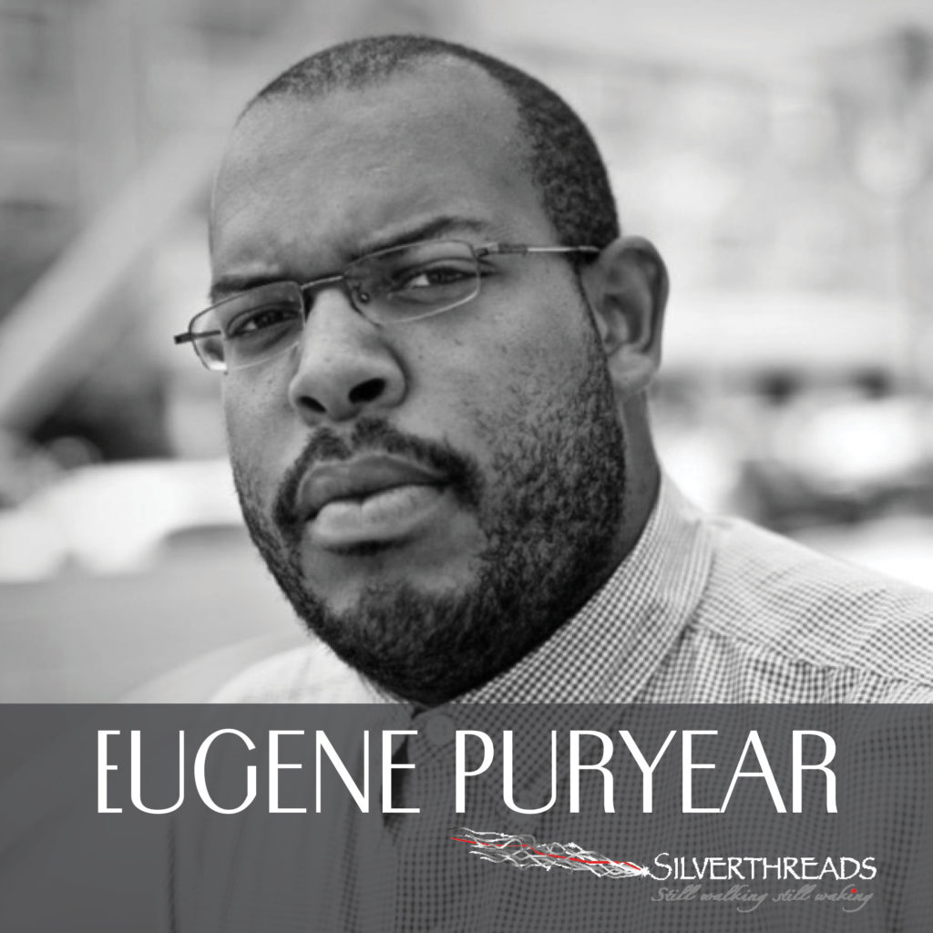 """Black and white photo of Eugene looking directly at the camera. Eugene is wearing glasses and a collared shirt. The image is cut off just below his shoulders. Across the bottom there is a transparent grey box that holds white text that reads """"Eugene Puryear"""" and the silverthreads logo is in the bottom right corner"""