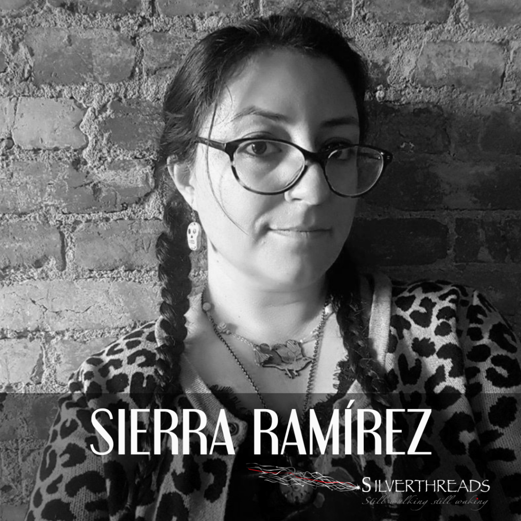 """Black and white photo of Sierra Ramírez from the shoulders up, against a brick wall. She is wearing a long braids, wide-frame glasses, and a leopard print cardigan over a black shirt. The text reads """"Sierra Ramírez"""". There is a Silver Threads logo in the bottom right corner."""