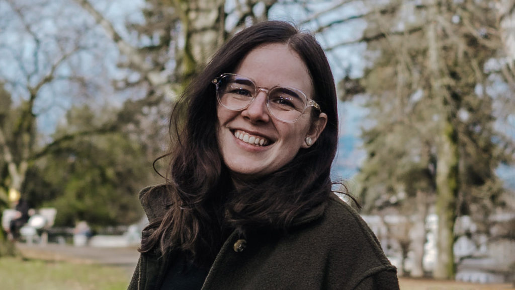 Photo of Melissa from the shoulders up, smiling into the camera. She is standing in a park with trees behind her. Her hair is dark and slightly waved. She is wearing wide clear frame glasses, a black turtleneck, and a green fleece jacket with a collar.