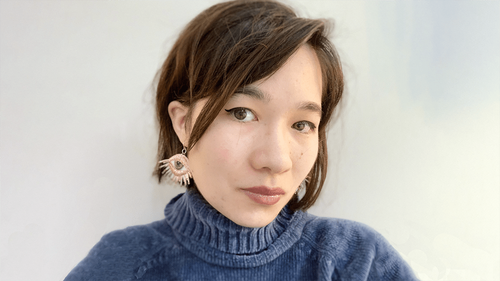 Photo of Rebecca from the shoulders up, head slightly tilted, looking unsmiling into the camera. She has her hair cut short and is wearing dangling earrings in the shape of eyes. She is wearing a dark blue, ribbed, turtleneck sweater.