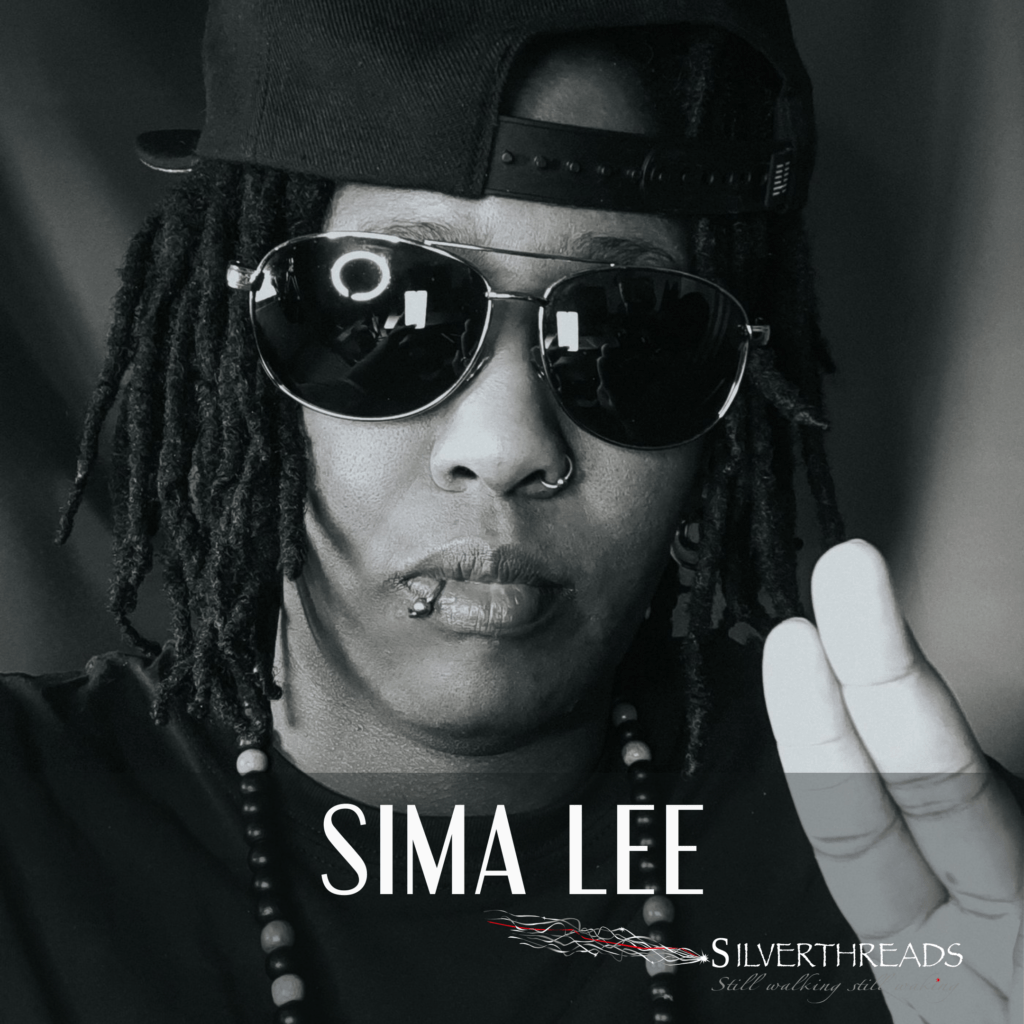 A black and white headshot photo of Sima Lee. She is wearing a ballcap on backwards, medium length black hair. She has a Lip ring and shiny sunglasses on. She is wearing a black tee-shirt. She has beads on. She has one hand up in a peace symbol taking up ⅓ of the lower right side of the image. Below is her name in white font, SIMA LEE, and under her name, to the right is the Silver Threads logo.